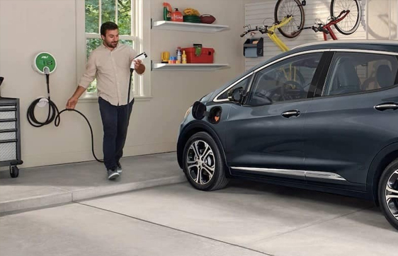 Man Bringing Charding Cable Towards Electric Car In Garage