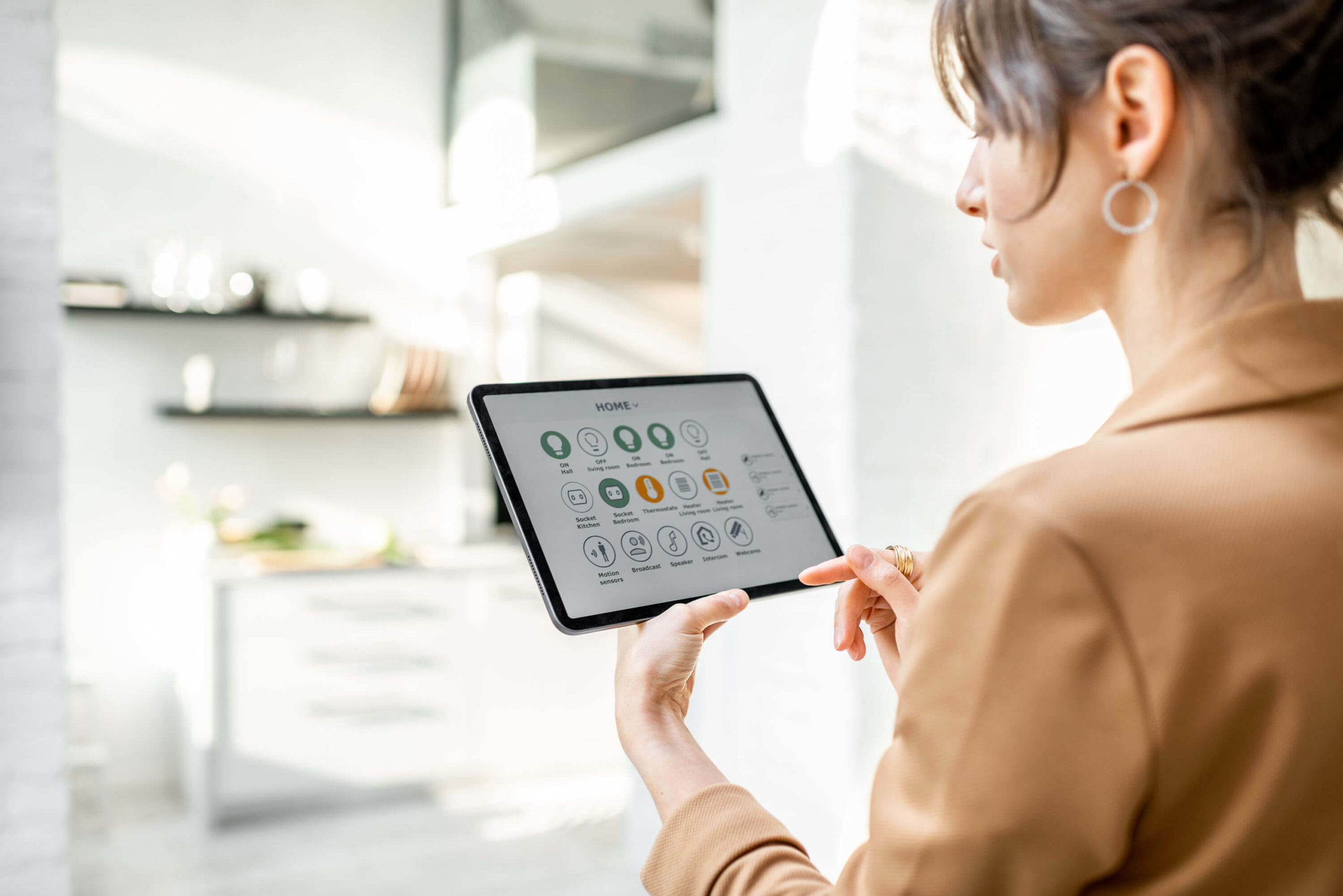 Woman controlling smart home devices using a digital tablet with launched application in the white living room. Smart home concept.